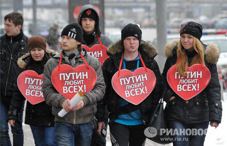 "Several dozens of Vladimir Putin's supporters gathered along Zubovsky boulevard in central Moscow on Sunday wearing heart-shaped signs that said ""Putin loves everyone."""