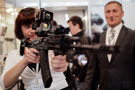 Vladimir Putin has supported the idea of merging the Izhmash and Izhmekh enterprises as part of the Russian Technologies State Corporation and under the Kalashnikov brand name. Photo: A young woman holds a Kalashnikov AK-103 assault rifle with a TN-1 thermal imaging sight at the International Exhibition of Police and Military Equipment (Interpolitex 2012) in Moscow.